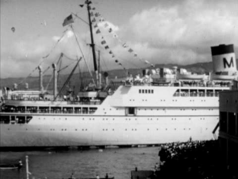 Cruise ship ocean liner moving in port VS People on ship waving young woman receiving lei traditional wreath of flowers from indigenous Hawaiian...