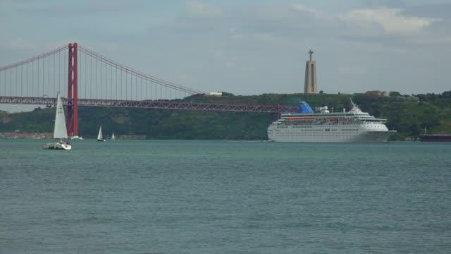 cruise ship on tagus river near the ponte 25 de abril, belem, lisbon, portugal - 4月25日橋点の映像素材/bロール