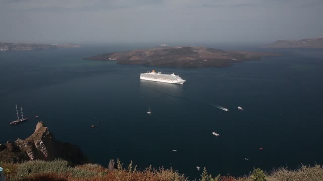 vidéos et rushes de cruise ship passes through a channel between a dormant volcano and the town of fira on the island of santorini, greece, on wednesday, may 20, 2015... - santorin