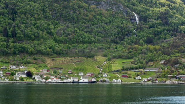 Cruise ship SIDE POV past waterfront village on Eidfjord, Norway