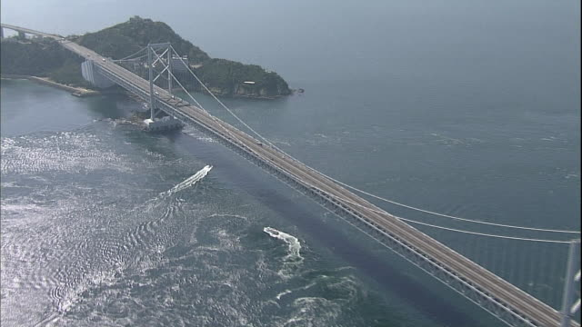 A cruise ship travels around a whirlpool beneath the Onaruto Bridge spanning the Naruto Strait in Japan.