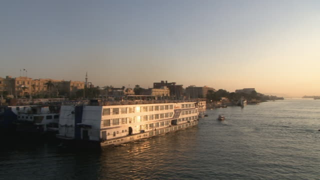 ws pan zi cruise ships and fellucas passing by in sunset / luxor, egypt - imbarcazione per passeggeri video stock e b–roll