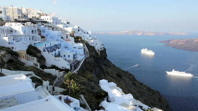 cruise ships in the bay overlooked by the white washed houses of thira, aegean sea on the island of santorini, greece, europe - mediterranean culture stock videos & royalty-free footage