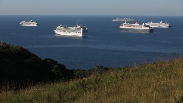 cruise ships moor since mid-march only a small handful of the world's 400 cruise ships has been able to accept passengersin in weymouth bay, u.k, on... - meadow stock videos & royalty-free footage