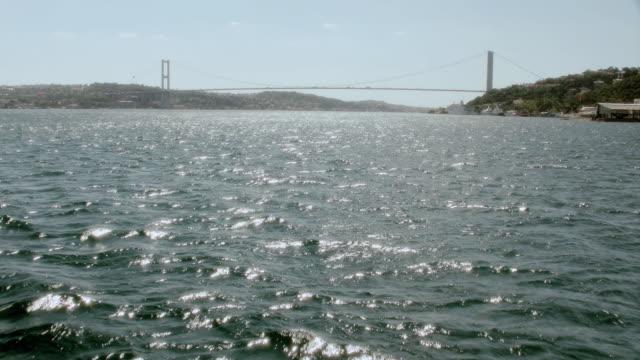 vídeos de stock e filmes b-roll de pov cruising over rippling waters towards the bosphorus bridge spanning the bosphorus strait / istanbul, turkey - estreito descrição física