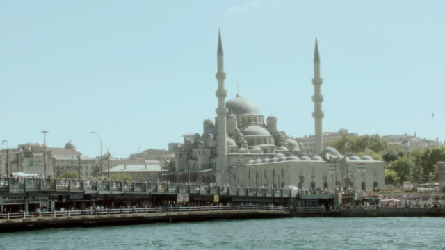 vídeos y material grabado en eventos de stock de pov cruising past a pier along the bosphorous strait with the sultan ahmed mosque in the distance / istanbul, turkey - formato buzón
