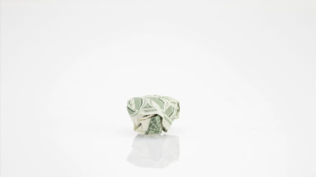 Crumpled one dollar bill rolling around against white background