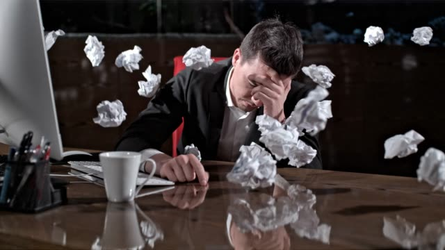 crumpled paper balls hitting exhausted businessman working late in office, super slow motion - crumpled paper stock videos and b-roll footage