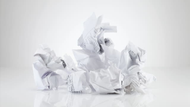 crumpled pieces of paper forming pile on white background - crumpled paper stock videos and b-roll footage