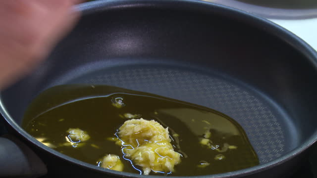 crushed garlic view of a cook adding olive oil to crushed garlic in a frying pan - garlic stock videos & royalty-free footage