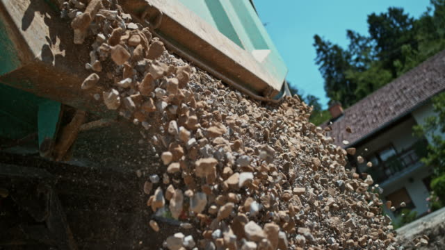 slo mo ld crushed rocks falling out of the truck unloading the rocks at the sunny construction site - construction material stock videos & royalty-free footage