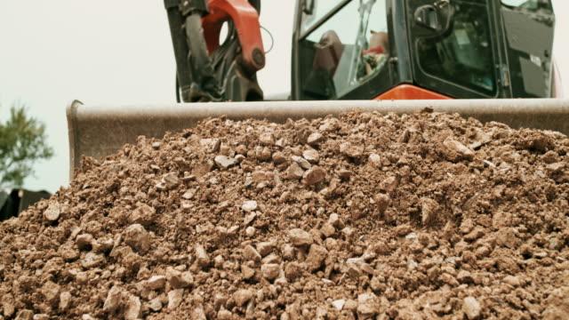 vídeos y material grabado en eventos de stock de slo mo picado rocas empujadas por la excavadora hacia la cámara - vehículo comercial terrestre