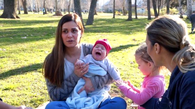 彼の妹と母によって落ち着いている赤ちゃんの少年を泣いて - 兄弟点の映像素材/bロール