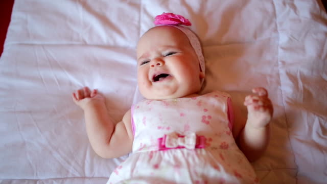 crying baby girl on the bed - lying on back stock videos & royalty-free footage