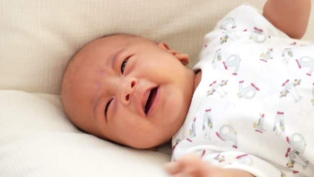 Crying baby on bed