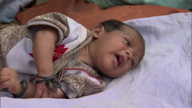 cu crying baby on blanket, agra, uttar pradesh, india - 男の赤ちゃん一人点の映像素材/bロール