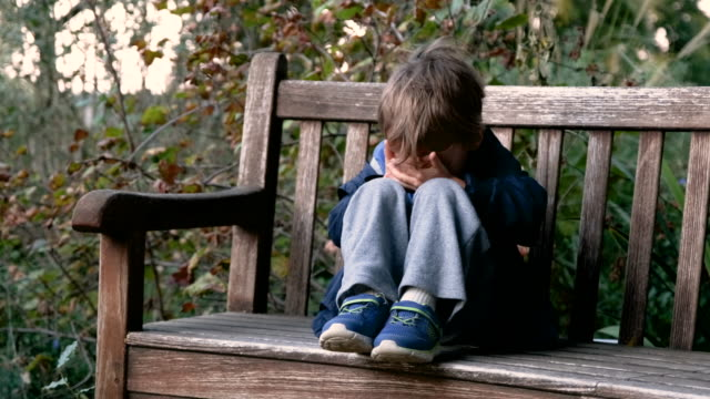 crying child boy sitting on a bench covering his face - child abuse stock videos & royalty-free footage