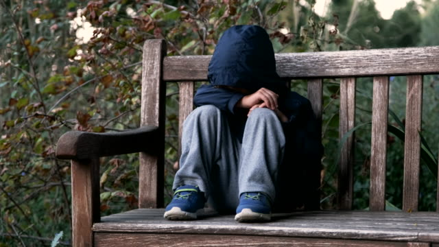crying child boy sitting on a bench covering his face - one boy only stock videos & royalty-free footage