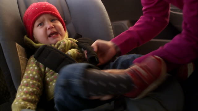 a crying child in a car safety-seat sweden. - cintura di sicurezza video stock e b–roll