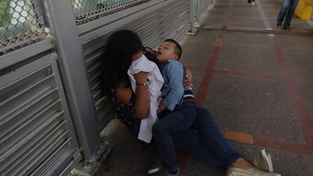 a crying honduran woman and her child after being denied entry into america at the border with texas - 中央アメリカ点の映像素材/bロール