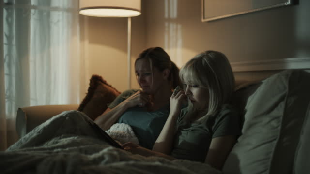 crying mother and daughter on sofa streaming sad movie on digital tablet / cedar hills, utah, united states - differential focus stock-videos und b-roll-filmmaterial