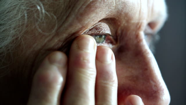 Crying old woman dries her eyes with hand