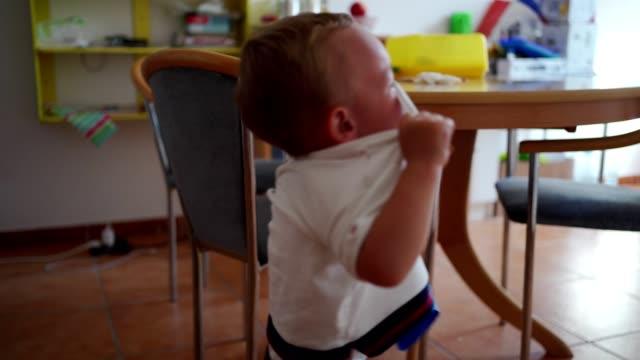 vídeos y material grabado en eventos de stock de llorando niño pequeño en la cocina - camiseta