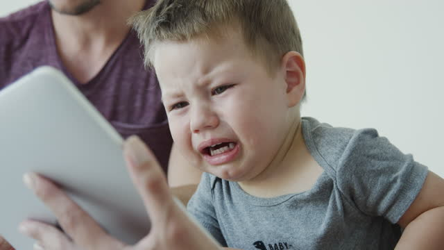 crying toddler looking at digital tablet while sitting with his parents on bed - fade in video transition stock videos & royalty-free footage