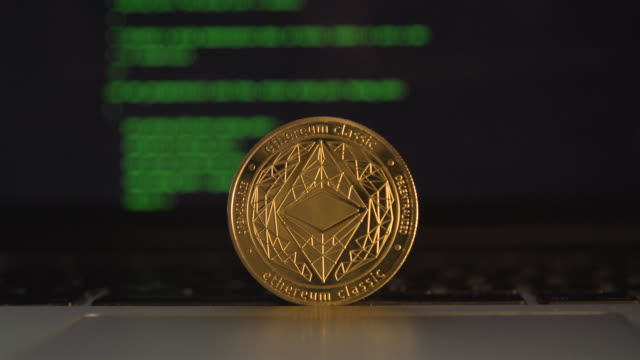 cryptocurrency ethereum in front a computer laptop coding screen close up - イーサリアム点の映像素材/bロール