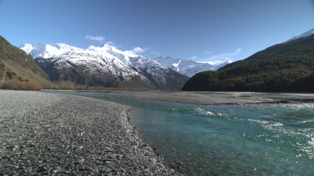 stockvideo's en b-roll-footage met crystal clear glacial river flowing over schist stone beach with snow capped view of mount aspiring in the distance - meer dan 50 seconden