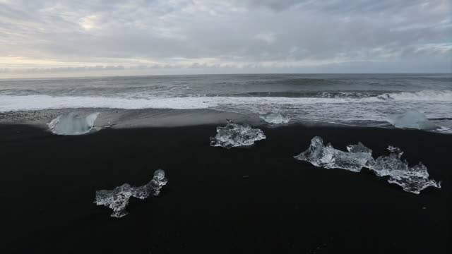 vídeos de stock, filmes e b-roll de crystal clear ice formations on a black sand beach. - ice crystal