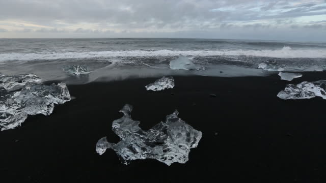 crystal clear ice formations on a black sand beach. - reykjavik stock videos and b-roll footage