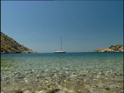 Crystal clear water gently laps the rocky shoreline a sailboat is moored in the background. Saronic Islands