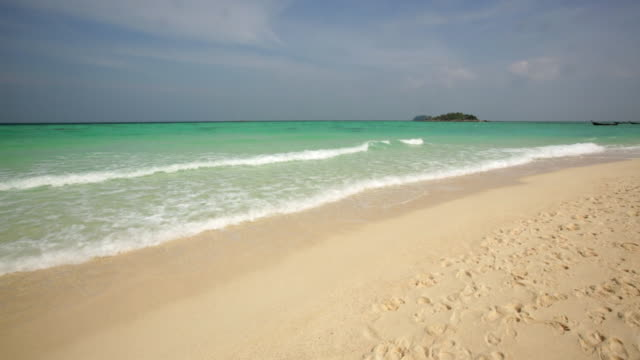 MS Crystal clear waves on Thai island on beach with paradise island in background