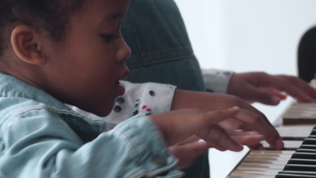 cu : african girl playing piano - piano stock videos & royalty-free footage