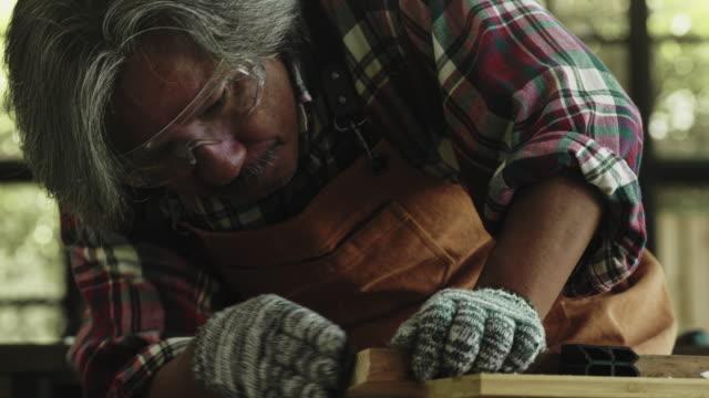 stockvideo's en b-roll-footage met cu: aziatische senior timmerman werken - carving craft product