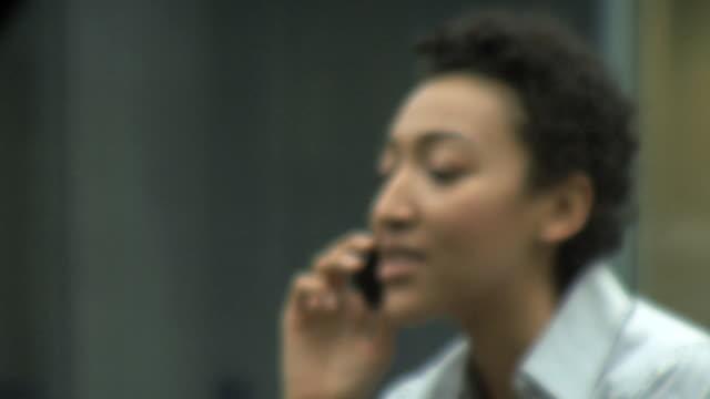 cu female on phone focus out in; uk - アフリカ系カリブ人点の映像素材/bロール