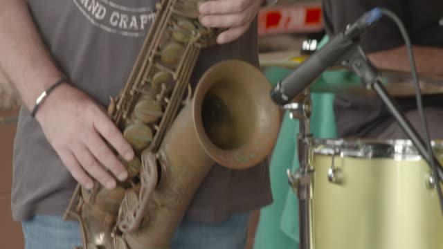vídeos de stock, filmes e b-roll de mute cu hands of anon man playing electric guitar pan to close up anon man plays saxaphone - dedilhando instrumento