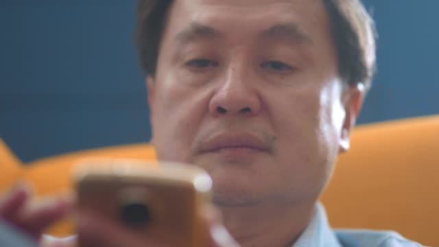 cu : mature man and smartphone - sad old asian man stock videos & royalty-free footage
