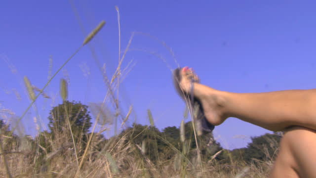 cu of a woman's legs in the air; uk - sandal stock videos and b-roll footage