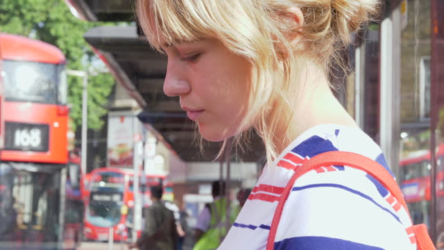stockvideo's en b-roll-footage met cu of commuter looking at her phone while waiting for bus. - bushalte