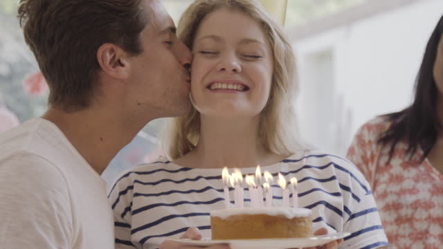cu of man presents birthday cake to woman with a kiss, she blows out candles while friends are cheering. - birthday gift stock videos & royalty-free footage