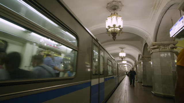 cu pan of train departing in station a moscow's underground metro - metropolitana video stock e b–roll