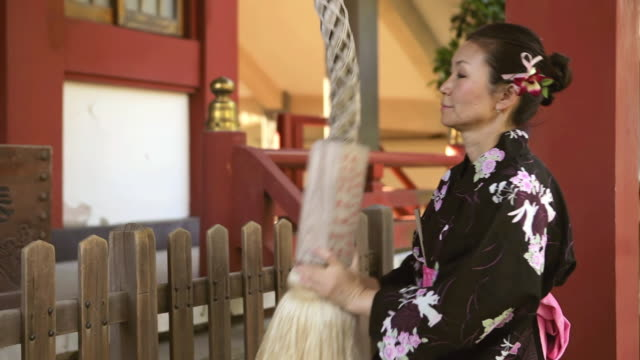 cu shot of mature asian woman in yukata (japanese costume) rings shinto bell and then prays and makes wish / tokyo, japan - shrine stock videos and b-roll footage