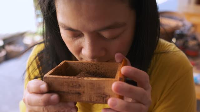cu zeitlupe asiatische frau geruch von kaffee pulver in holzkiste von schleifkaffee. - bean stock-videos und b-roll-filmmaterial
