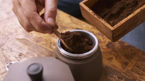 cu slow motiopn hand legen frisches gemahlenes kaffeepulver in die kaffeetafel des moka-topfes. - kaffee stock-videos und b-roll-filmmaterial