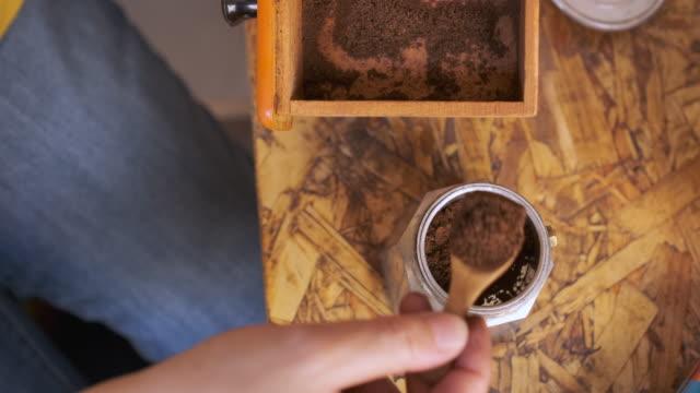 vídeos de stock e filmes b-roll de cu slow motiopn hand put fresh ground morning coffee powder in to coffee tablet of moka pot - fazer