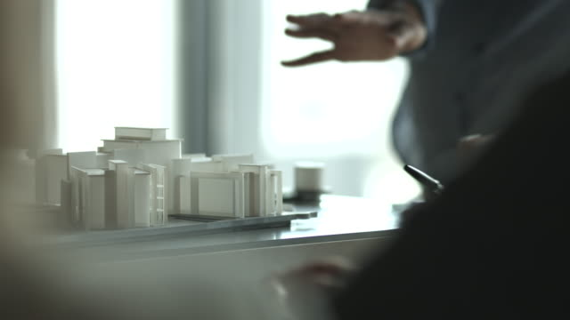 cu_architects discussing over model of building project - architetto video stock e b–roll
