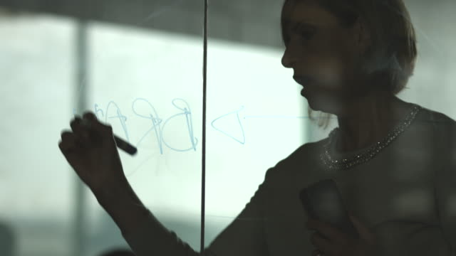 CU_Businesswoman writing branding strategy on glass wall