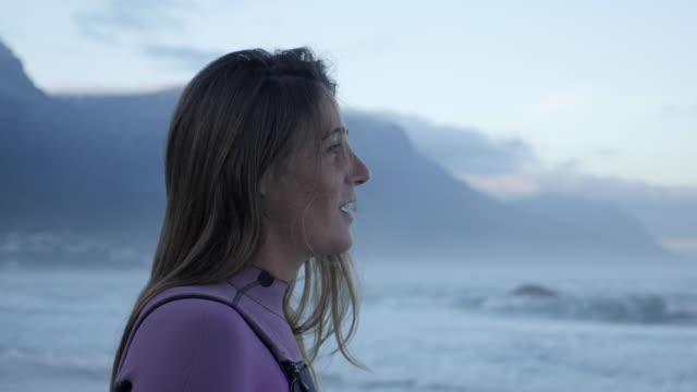 cu_female surfer looking at the ocean - wetsuit stock videos & royalty-free footage